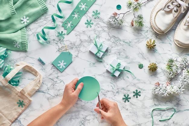 Inverno, piatto creativo con varie decorazioni invernali, ramoscelli di albero di natale e tag per il taglio delle mani