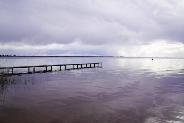 Inverno vuoto dell'acqua blu di alba del pontone di accesso di legno sul lago hourtin in gironda francia