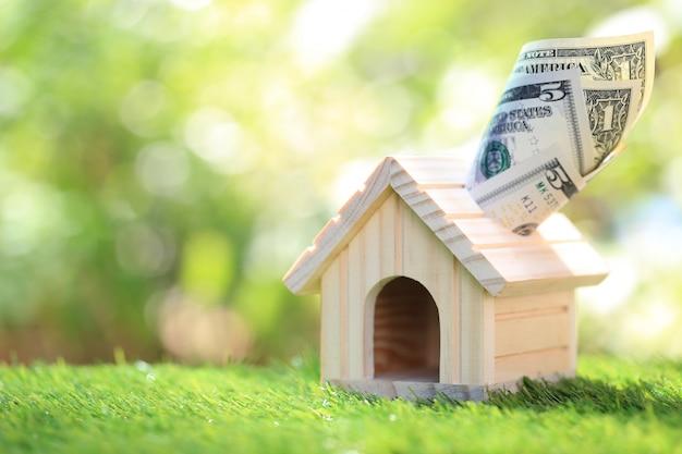 Investimenti aziendali e immobiliari, modello casa con banconote, risparmio per preparare in futuro
