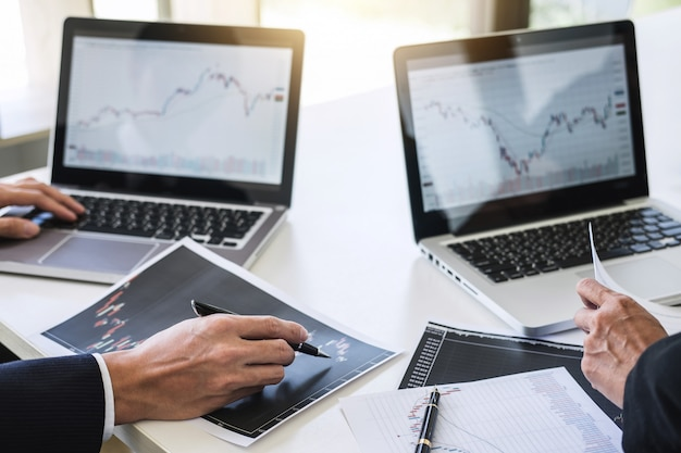 Investimento del gruppo di affari che lavora con il commercio del mercato azionario del grafico di analisi e del computer
