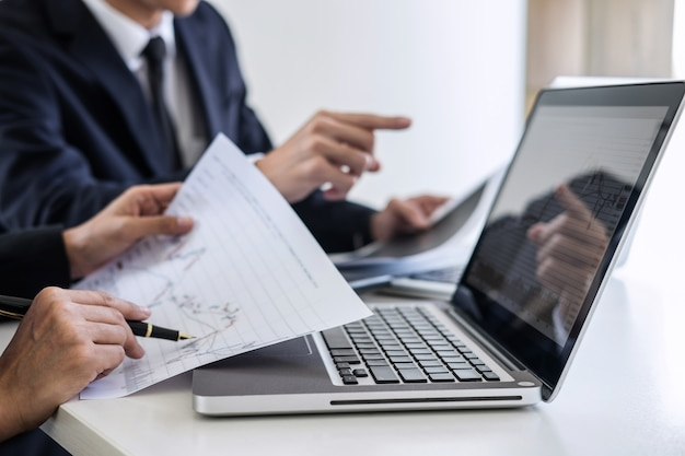 Investimento del gruppo di affari che lavora con il mercato azionario del grafico di analisi e del computer che vende con il grafico