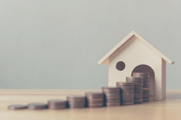 Investimento immobiliare e mutuo casa finanziaria moneta pila di denaro con casa in legno
