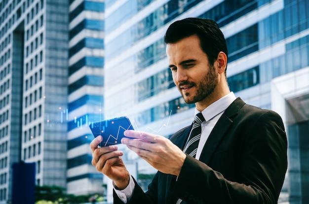 Investitore caucasico dell'uomo d'affari che utilizza i dati del mercato azionario di controllo del telefono cellulare con il grafico grafico del bastone della candela grafico dell'investimento del mercato azionario per il commercio di forex, rete internet, concetto di tecnologia