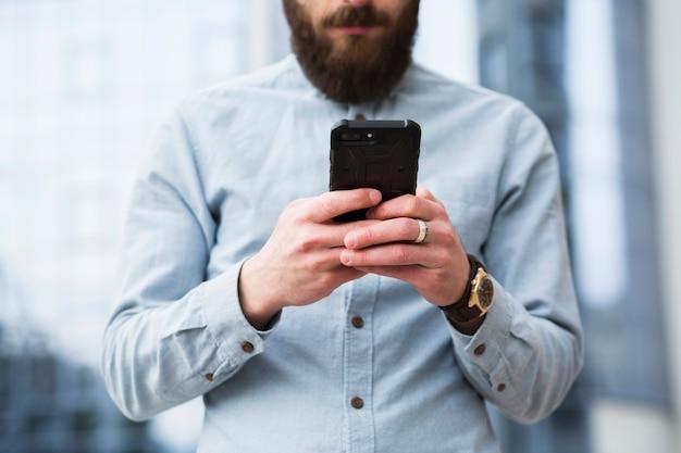 Invio di messaggi di testo barbuto del giovane sul telefono cellulare