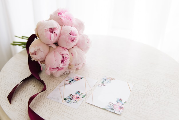 Inviti di nozze accanto a un bellissimo bouquet di peonie rosa