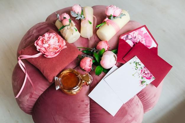 Inviti di nozze, candele e peonie giacciono su una bella sedia morbida