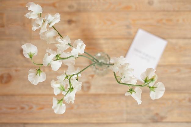 Invito di nozze certificato di compleanno per una spa o cura decorata carta di lettera su un tavolo di legno bianco con un ramo di fiori bianchi.