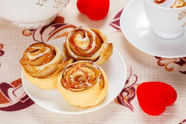 Involtini al forno rubicondo su un piatto bianco con una tazza di tè alla mela frutta