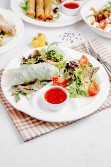 Involtini di cavolo con verdure e salsa sul tavolo