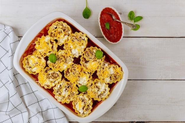 Involtini di lasagne a base di carne macinata e ricotta e salsa di pomodoro.