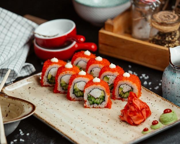 Involtini di sushi con caviale rosso in cima, zenzero e wasabi.