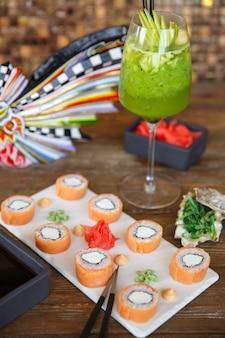 Involtini di sushi di salmone serviti con wasabi e zenzero