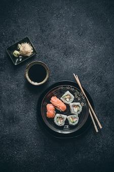 Involtini di sushi fantasia con salsa wasabi, zenzero e soia sulla superficie nera.