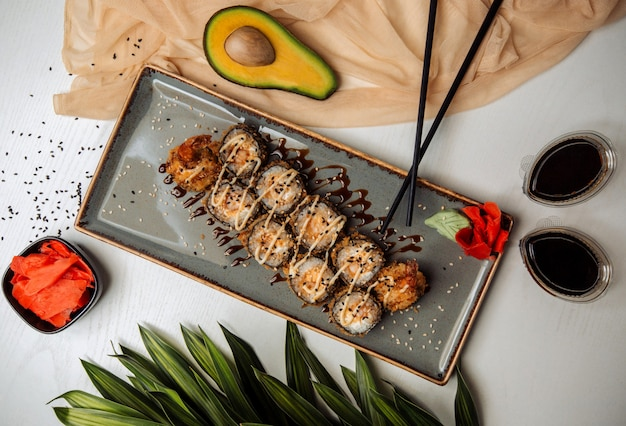 Involtini di sushi fritti guarniti con sesamo, salsa teryaki, serviti con wasabi e zenzero