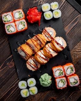 Involtini di sushi maki caldi e involtini di california serviti con zenzero e wasabi