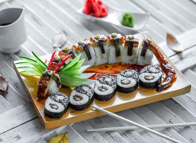 Involtini di sushi unagi serviti a forma di drago e sushi yin yang