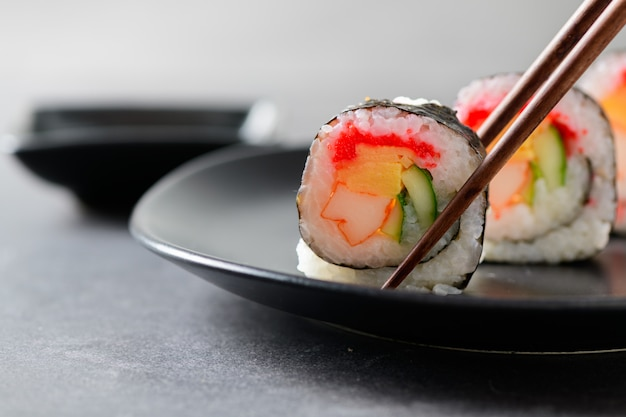 Involtini di sushi (verdure, inari e bastoncini di granchio) con le bacchette