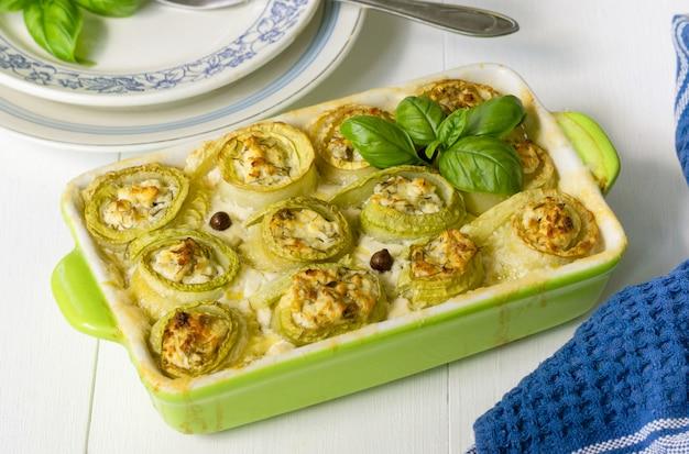 Involtini di zucchine al forno con ricotta, erbe e panna acida in un piatto di ceramica