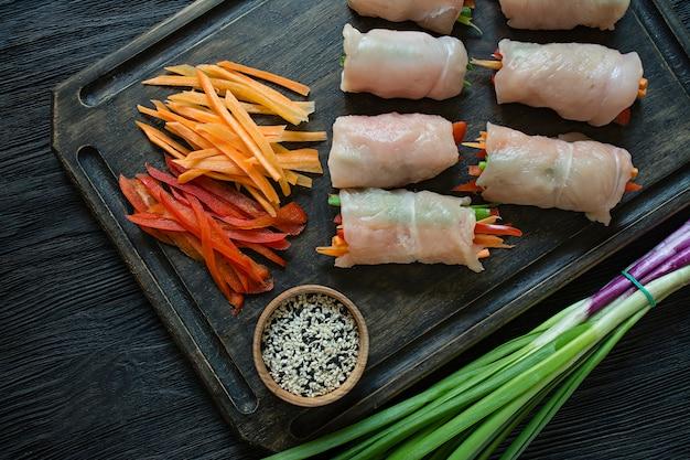 Involtini fatti in casa con petto di pollo fresco con verdure, fette di carota, peperone su un tagliere scuro.
