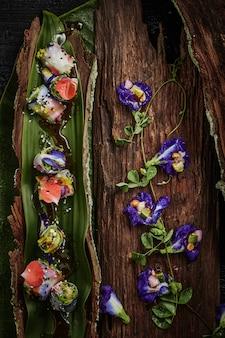 Involtini primavera con fiori e foglie avvolte.