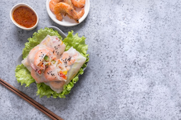 Involtini primavera con gamberi e verdure su grigio. avvicinamento. cucina asiatica.
