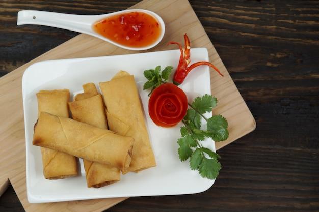Involtini primavera fritti cinesi serviti con salsa di peperoncino rosso sul bordo di legno sul tavolo di legno scuro