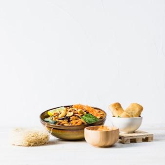 Involtini primavera una ciotola di spaghetti tailandesi con gamberetti e vermicelli