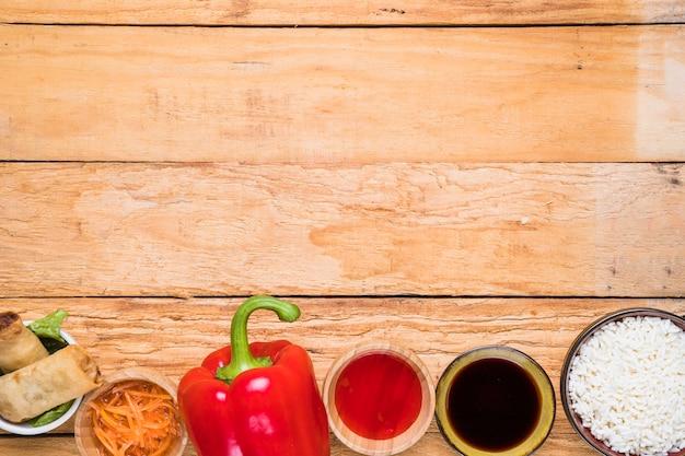 Involtino primavera; peperone rosso; salse e ciotola di riso sulla scrivania in legno