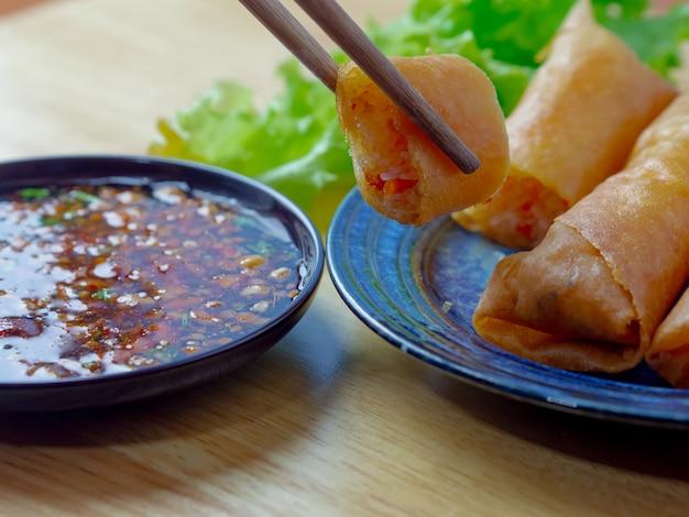 Involtino primavera thailandese con treccia, maiale, fettina di pollo e fuoco nell'olio con salsa piccante