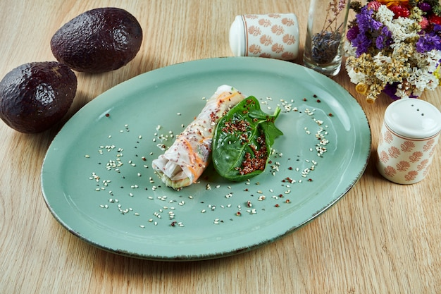 Involtino primavera vegetariano con quinoa, carote e spinaci su un piatto blu su un tavolo di legno. cibo di strada tailandese. fitness e dieta sana. avvicinamento.