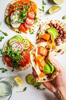 Involucri aperti della tortiglia del vegano con la patata dolce, i fagioli, l'avocado, i pomodori, la zucca ed i germogli su fondo bianco, disposizione piana. concetto di cibo sano vegan.