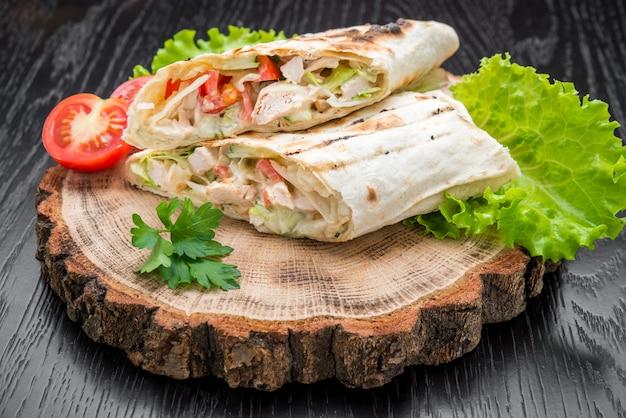 Involucri della tortiglia con il pollo arrostito su un fondo di legno.