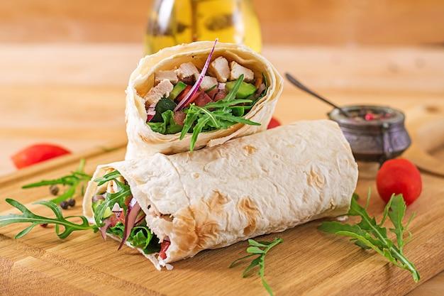 Involucri delle tortillas con pollo e verdure su superficie di legno. burrito di pollo cibo salutare.