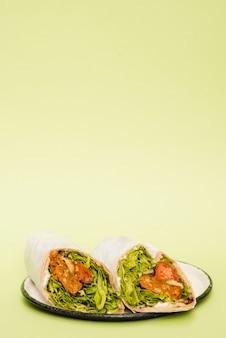 Involucro del burrito del pollo sul piatto contro il fondo di verde della menta