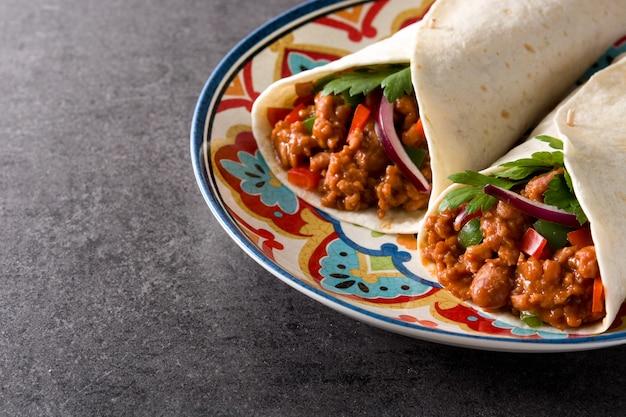 Involucro tipico del burrito messicano con manzo, frijoles e verdure sul nero