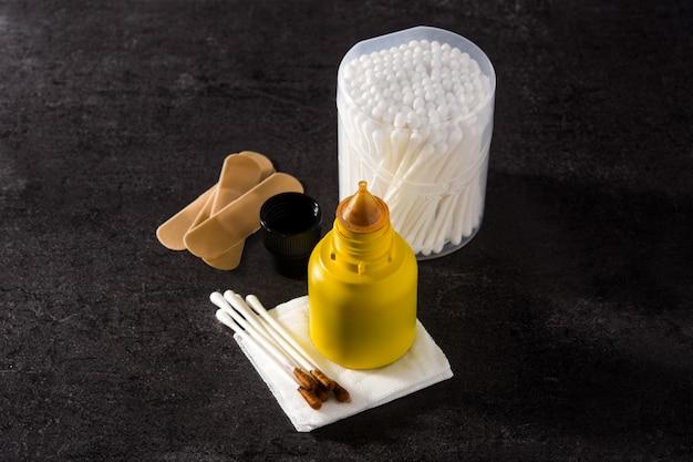 Iodio medico in una bottiglia e garze sul tavolo nero