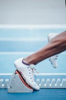 Irriconoscibile afro sportiva in abbigliamento sportivo che inizia la corsa dalla posizione di partenza accovacciata sui blocchi di partenza