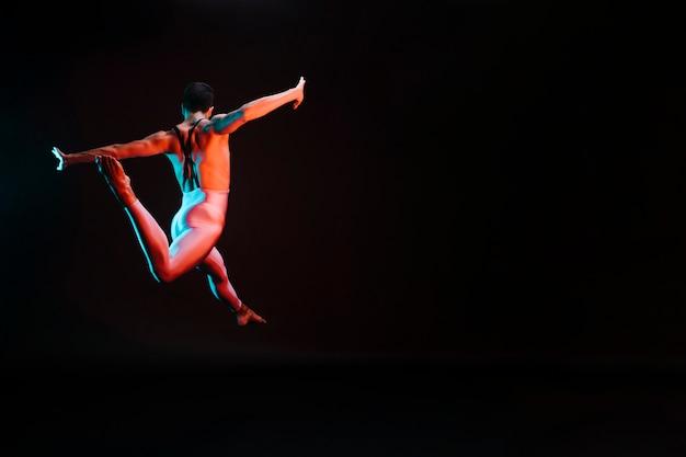Irriconoscibile ballerino che salta con le braccia aperte e fa divisioni