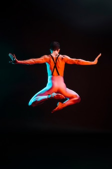 Irriconoscibile ballerino che salta con le braccia aperte sotto i riflettori