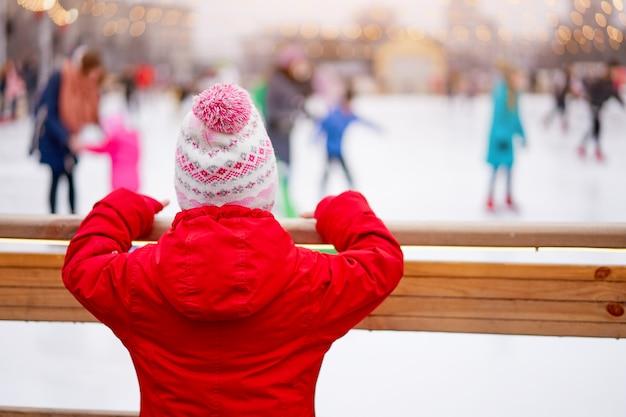 Irriconoscibile bambina in piedi vicino anello di pattinaggio su ghiaccio tempo di vacanze invernali