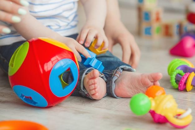 Irriconoscibile bambino plaing con giocattoli colorati