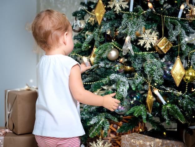 Irriconoscibile piccolo bambino tocca la decorazione dell'albero di natale