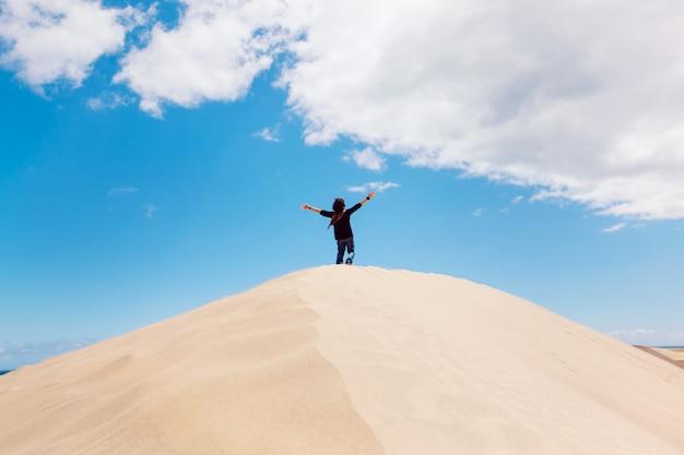 Irriconoscibile uomo con le braccia spalancate sulla cima di una duna del deserto. uomo che gode della libertà.