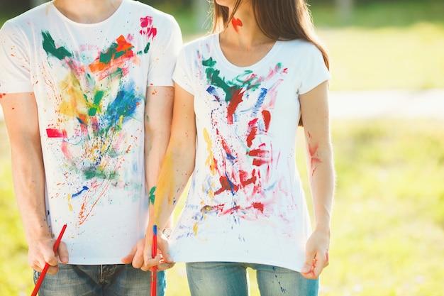 Irriconoscibile uomo e donna che scuotono le magliette colorate dipinte a porte chiuse e sorridenti. ragazzo e ragazza graziosi divertendosi all'aperto.