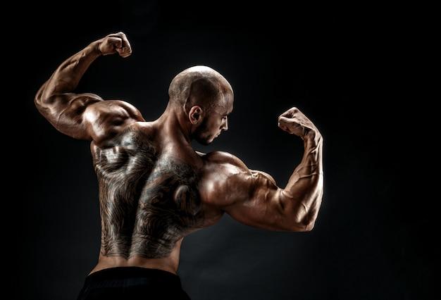 Irriconoscibile uomo muscoloso con tatuaggio sulla schiena contro di sfondo nero. isolato.