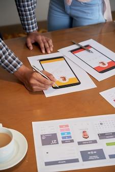 Irriconoscibili colleghi in piedi al tavolo e guardando progetti di design