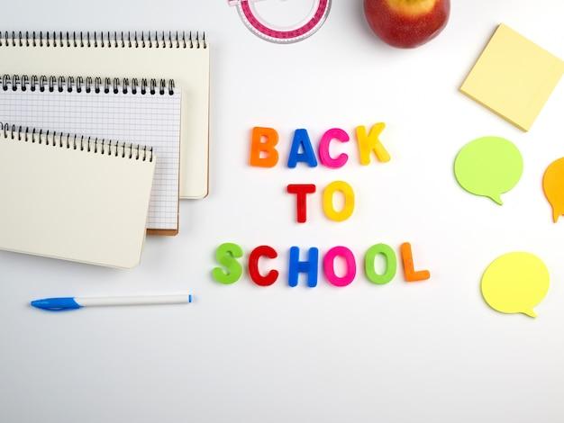 Iscrizione a scuola da lettere in plastica multicolore e una pila di quaderni