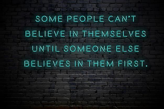 Iscrizione al neon della frase motivazionale positiva positiva contro il muro di mattoni