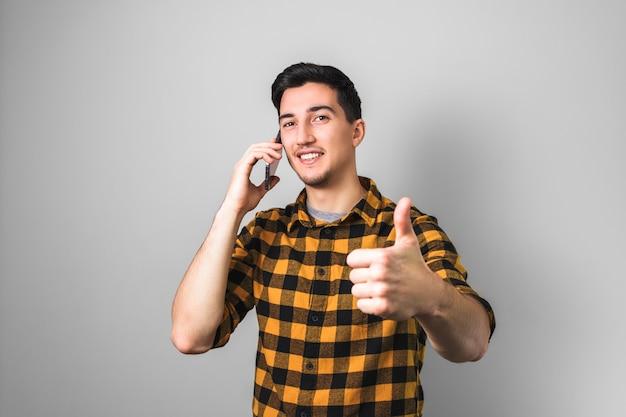 Iscrizione all'università bel giovane o studente con un sorriso sul viso, parlando al telefono e mostrando grande pollice in su