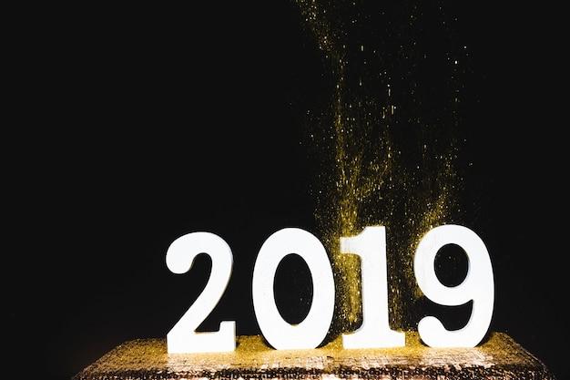 Iscrizione bianca 2019 con paillettes dorate sul tavolo